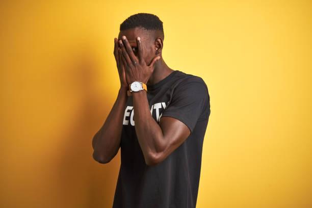 hombre de protección afroamericano que lleva uniforme de seguridad sobre fondo amarillo aislado con expresión triste cubriendo la cara con las manos mientras llora. concepto de depresión. - vergüenza fotografías e imágenes de stock