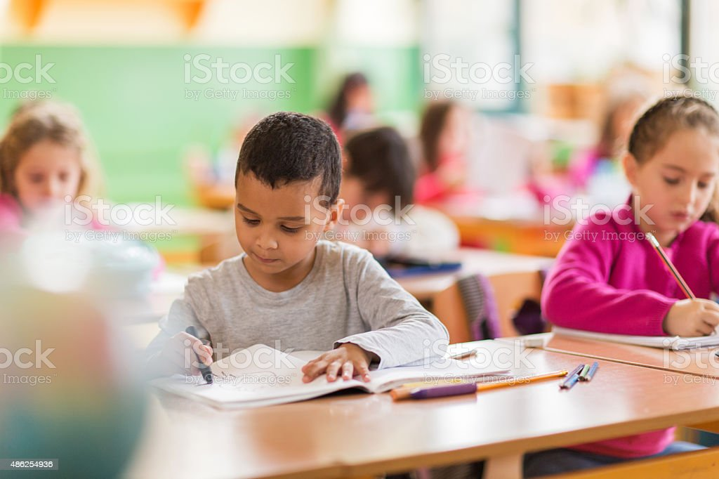 African American schoolboy drawing on a class at school. stock photo