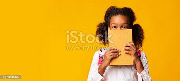 Shy African American Schoolgirl Covering Face With Book On Yellow Background In Studio. Panorama With Empty Space