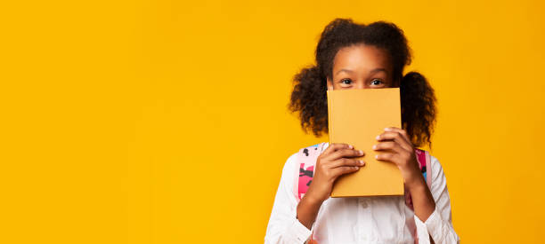 African American Schoolgirl Covering Face With Book, Yellow Background Shy African American Schoolgirl Covering Face With Book On Yellow Background In Studio. Panorama With Empty Space reading stock pictures, royalty-free photos & images