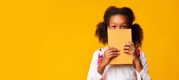 face da coberta da estudante do americano africano com livro, fundo amarelo - reading - fotografias e filmes do acervo