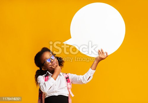 I Think. Pensive African American Schoolgirl Holding Speech Bubble Overhead On Yellow Studio Background. Mockup, Free Space
