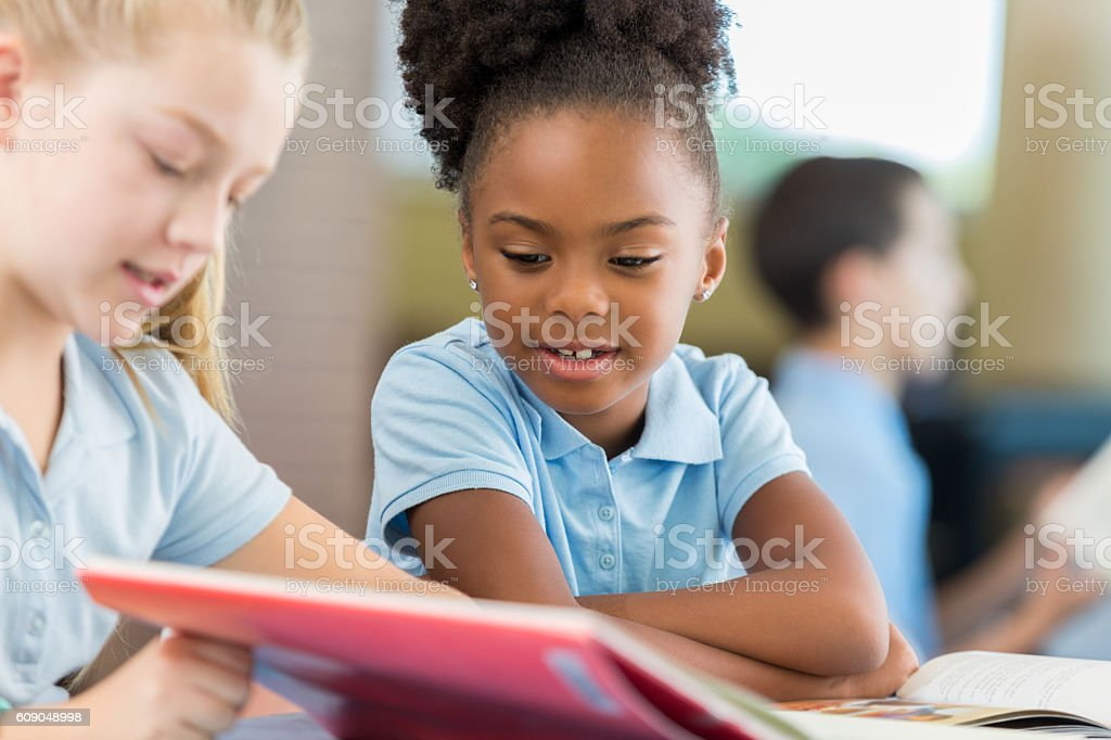 African American schoolgirl reading a book with her Caucasian classmate – Foto