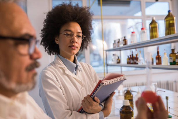 African American scientist cooperating with her male colleague in a laboratory. stock photo