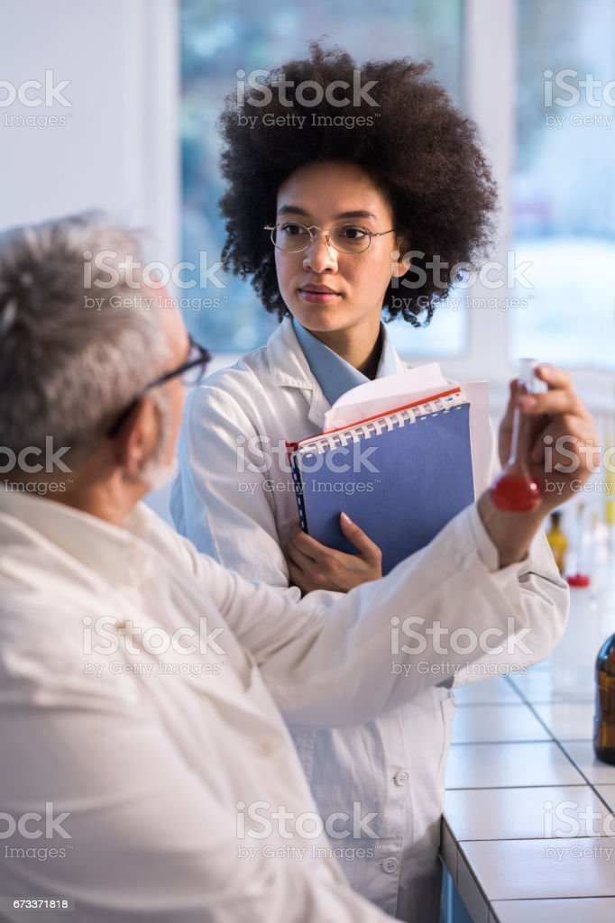 African American scientist discussing about medical research with mature colleague. stock photo