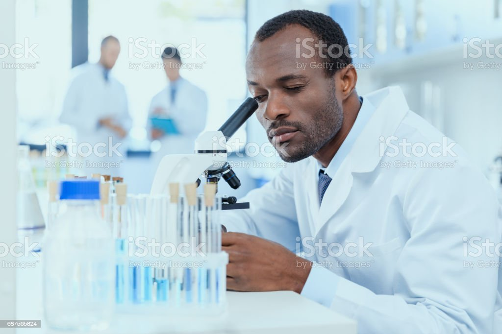African american scientist in white coat working with microscope in laboratory, laboratory researcher concept stock photo