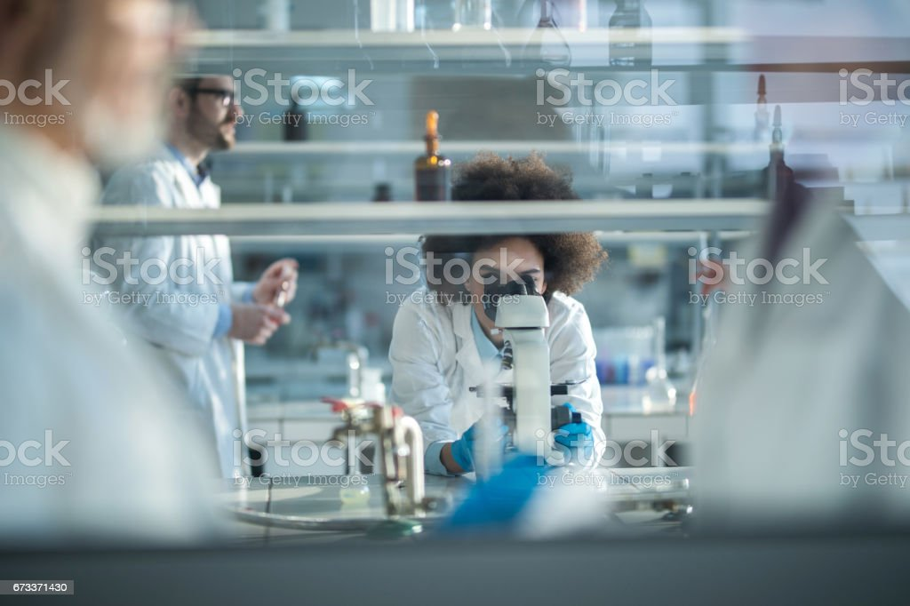 African American scientist looking through microscope while working in laboratory with colleagues. stock photo