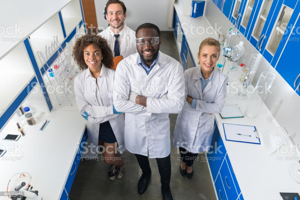 African American Scientist With Group Of Researchers In Modern Laboratory Happy Smiling, Mix Race Team Of Scientific Researchers In Lab stock photo