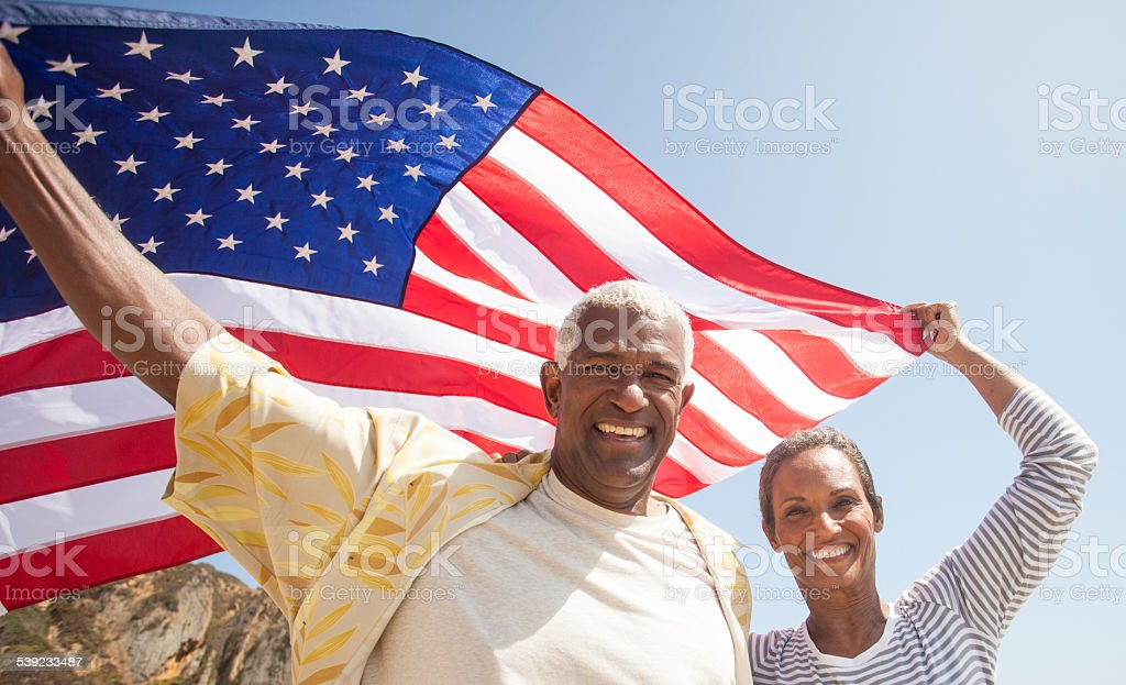 African American Senior Couple Carrying USA Flag stock photo