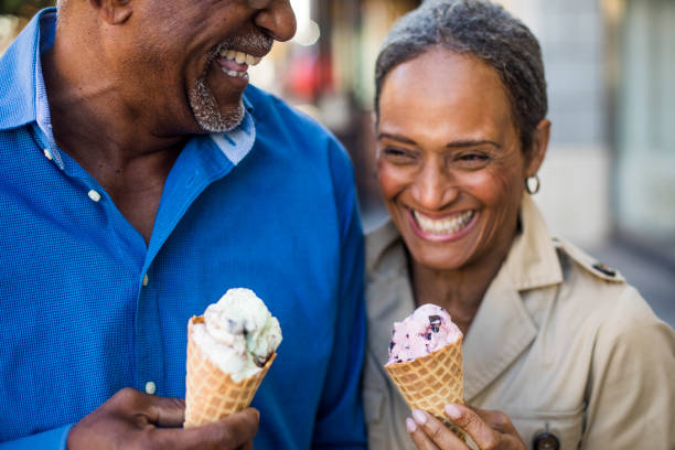 african american senior couple on the town with ice cream - senior valentine stock photos and pictures
