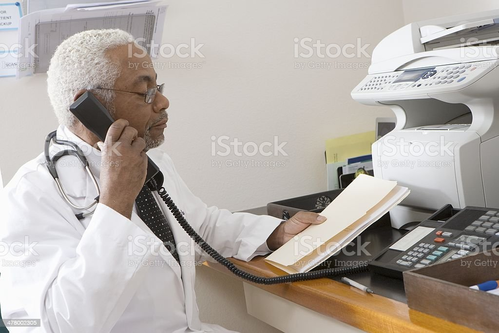 African American senior male doctor holding document while using phone stock photo