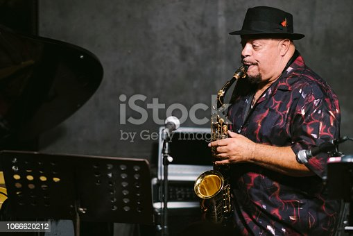 An African American senior man is playing the saxophone at stage during a jazz music concert.