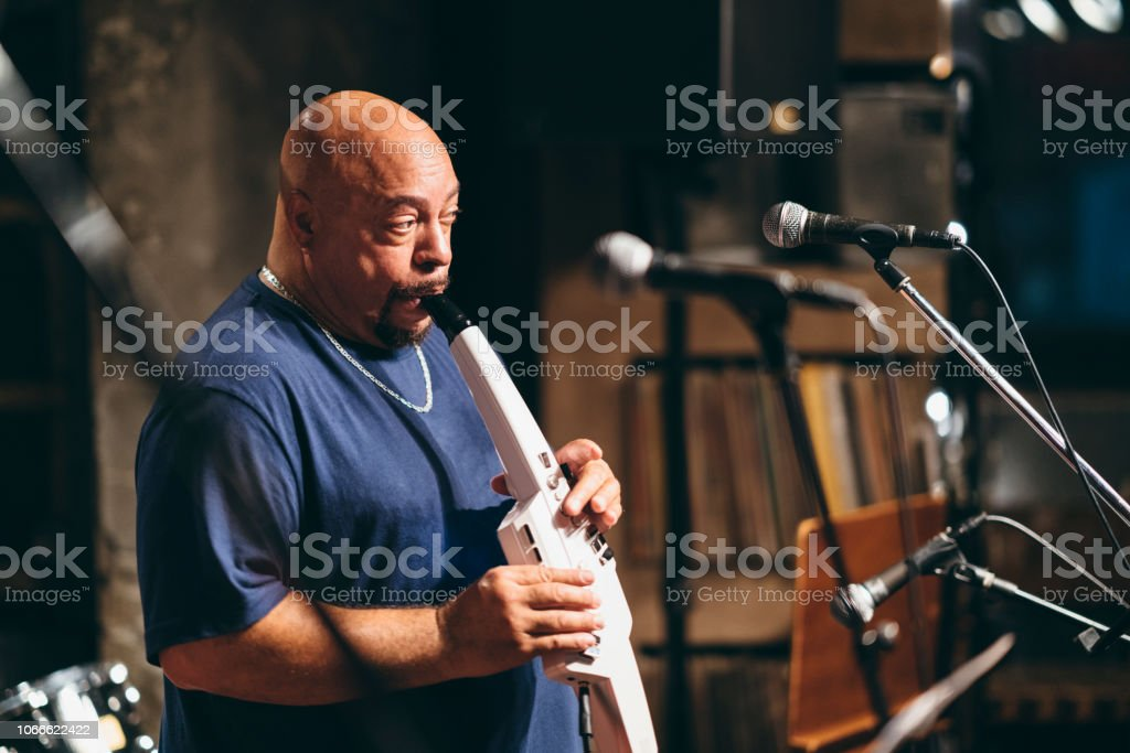 An African American senior man is playing the saxophone at stage...