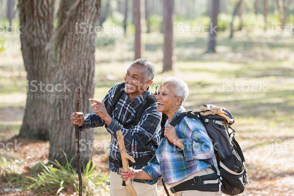 African American seniors hiking through woods stock photo