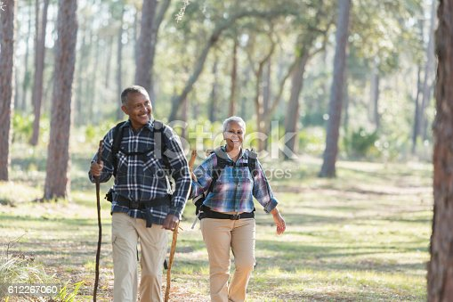 An African American senior couple hiking through the woods. They are wearing pants and plaid shirts, carrying walking sticks and backpacks. The focus is on the woman who is walking a few paces behind the man.