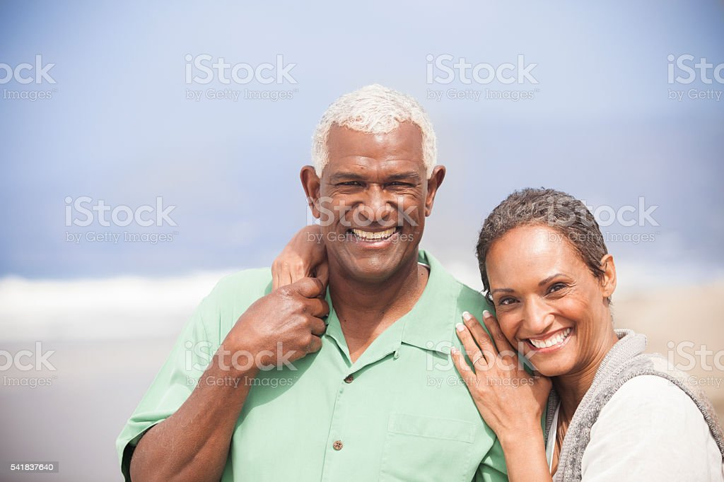 African American Seniors Smiling Together on Beach stock photo