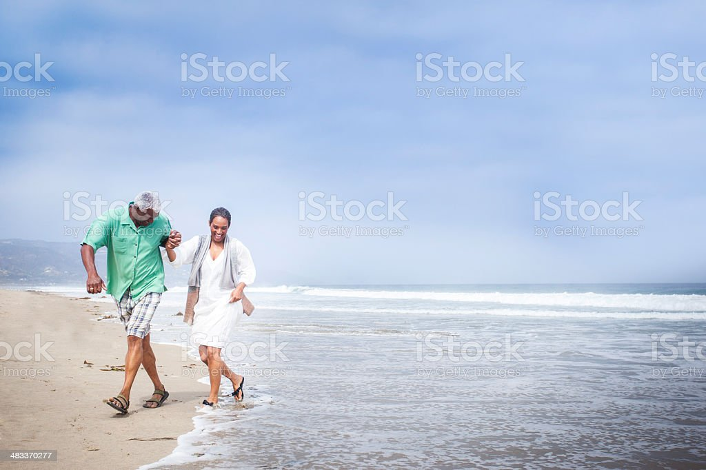 African American Seniors Walking on Beach stock photo