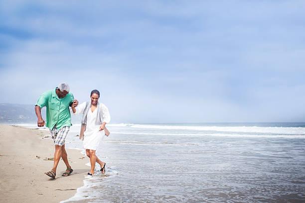 African American Seniors Walking on Beach stock photo