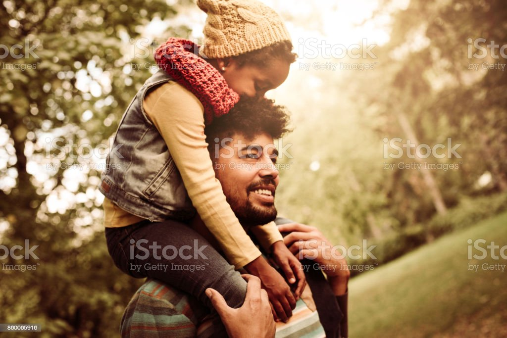 African American single father carrying daughter on shoulders trough...