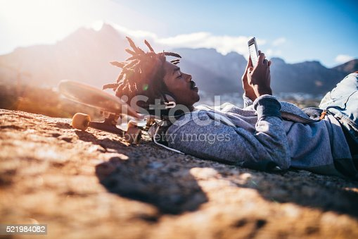 istock African American Skater Resting and Looking at Smartphone at Sea 521984082