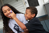 African American son placing I Voted Early Sticker on smiling black mother's face