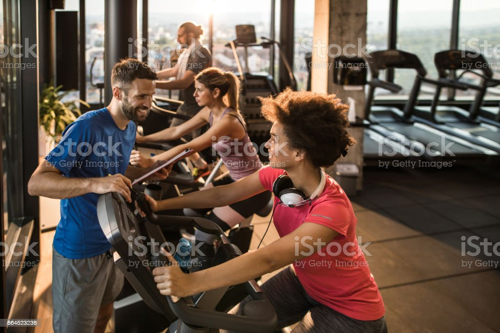 African American sportswoman talking to her coach during spinning class in a gym. stock photo