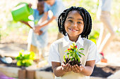African American elementary age little girl is smiling and looking at the camera. She is holding a pepper plant that she is preparing to plant in soil in the school garden during an outdoor science class. Her classmates are using watering cans and gardening tools in the background. Students are wearing private school uniforms.