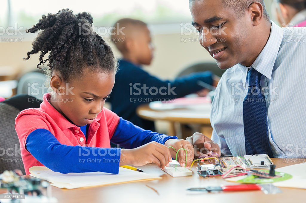 African American student learning about robotics during elementary class stock photo