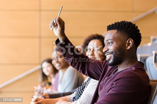 A confident male college student raises his hand to ask a question during class. He is smiling confidently.