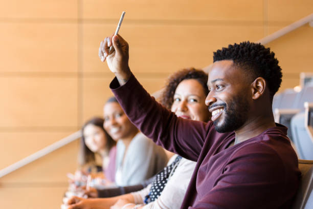 African American student raises his hand during class stock photo