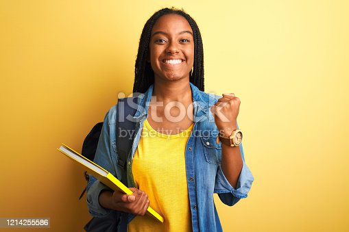 African american student woman wearing backpack and book over isolated yellow background screaming proud and celebrating victory and success very excited, cheering emotion