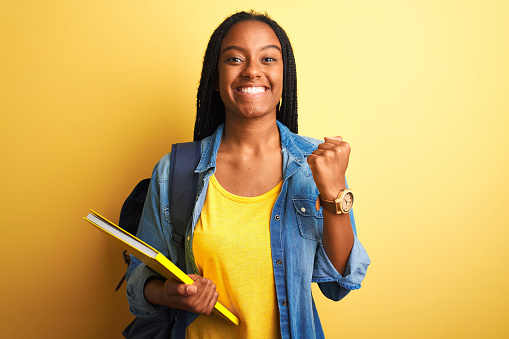 istock African american student woman wearing backpack and book over isolated yellow background screaming proud and celebrating victory and success very excited, cheering emotion 1214255586