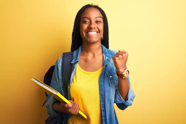 mujer estudiante afroamericana con mochila y libro sobre fondo amarillo aislado gritando orgulloso y celebrando la victoria y el éxito muy emocionado, animando la emoción - estudiante fotografías e imágenes de stock