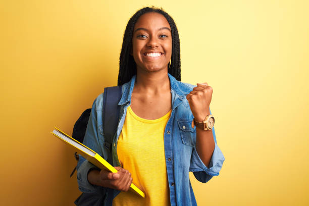 African american student woman wearing backpack and book over isolated yellow background screaming proud and celebrating victory and success very excited, cheering emotion stock photo