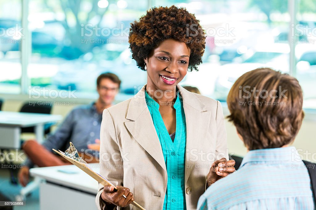 African American Teacher speaking to student stock photo