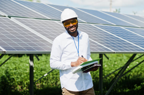 African american technician check the maintenance of the solar panels. Black man engineer at solar station. stock photo