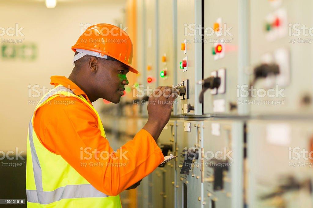 african american technician writing down machine setting data stock photo