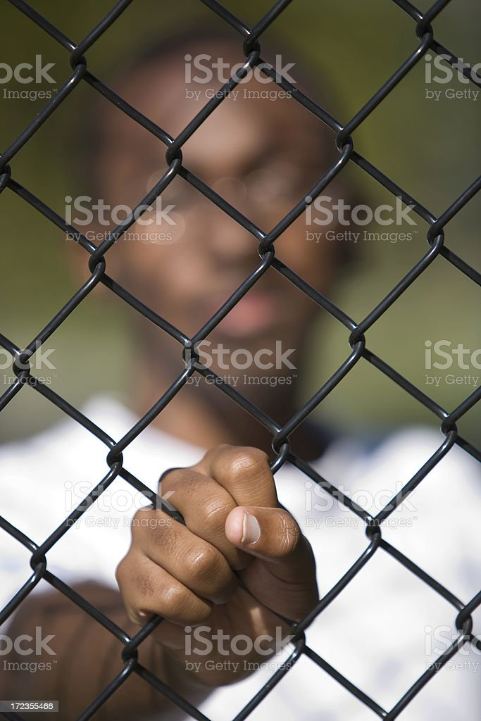 African American teen behind the fence royalty-free stock photo