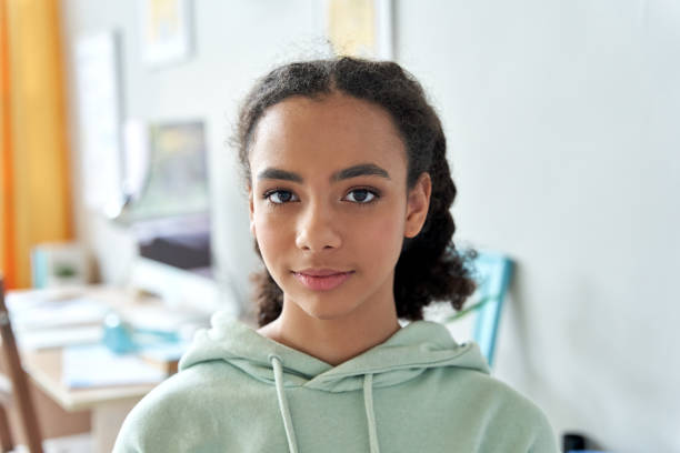 自宅でカメラを見ているアフリカ系アメリカ人の十代の女子高校生。ジェネレーションz混合レースかわいいティーンエイジャーは、寝室のカジュアルなインテリアに立って、ヘッドショット - gen z ストックフォトと画像