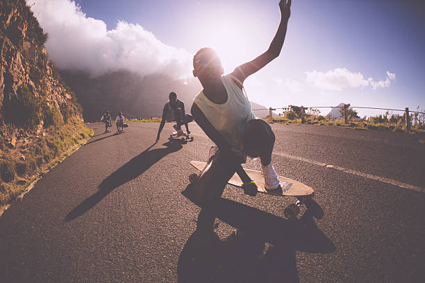 african american teen girl on a longboard doing downhill racing - skateboard bildbanksfoton och bilder