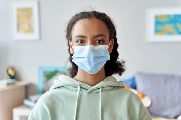 自宅でカメラを見てフェイスマスクを身に着けているアフリカ系アメリカ人の十代の女の子。パンデミック検疫コンセプト中の混血ティーンエイジャー。居心地の良い保護のための子供の安� - gen z ストックフォトと画像