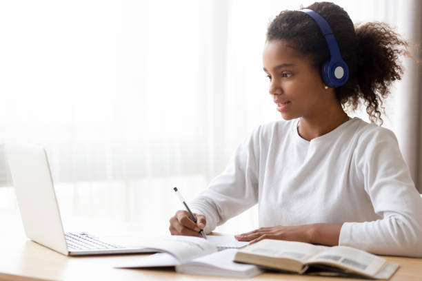 african american teen girl wearing headphones learning language online - didattica a distanza foto e immagini stock