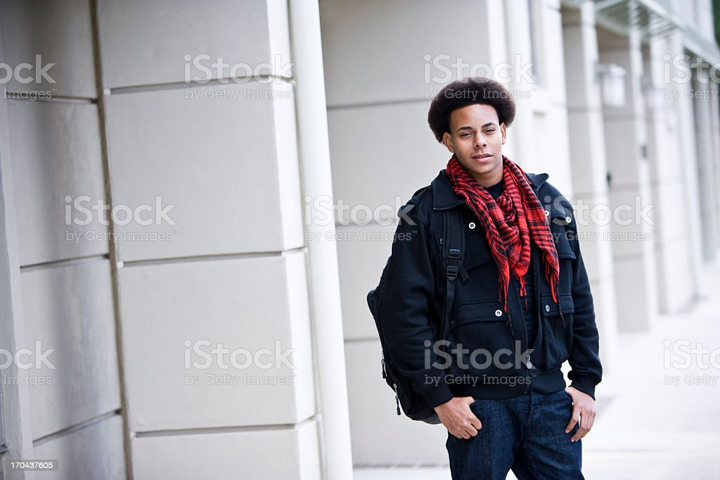 African American teenage boy standing outside building with back stock photo