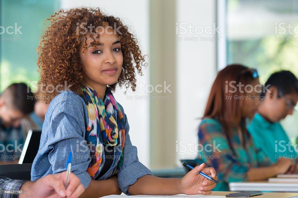 African American teenage girl smiling in classroom stock photo