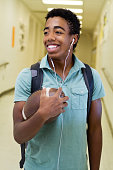 African American Teenage student walking down the hall and holding a football.