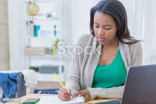istock African American teenager concentrates while working on homework assignment 688821536