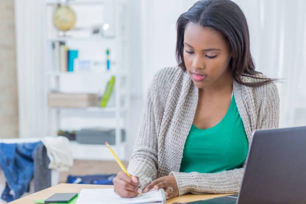 african american teenager konzentriert sich während der arbeit an hausaufgabe - schreibunterricht stock-fotos und bilder