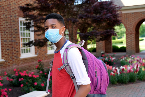 African American teenager wearing backpack and facial mask to protect himself from Coronavirus.