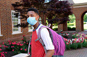 istock African American teenager wearing backpack and facial mask to protect himself from Coronavirus. 1225438107