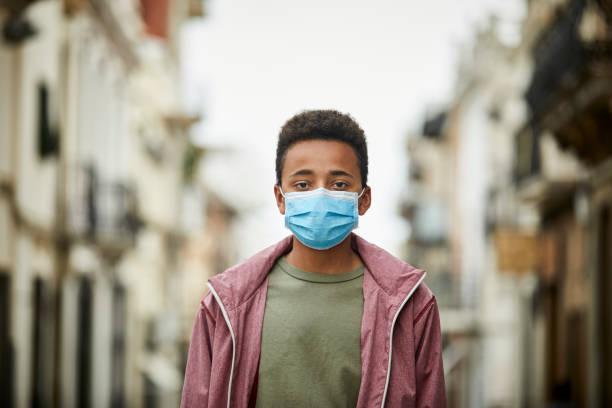 Afroamerikanischer Teenager mit Schutzmaske auf der Straße für COVID-19 Pandemie – Foto